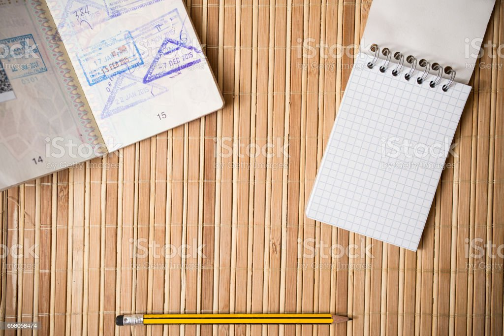 Passport, notepad and pencil on a bamboo table stock photo