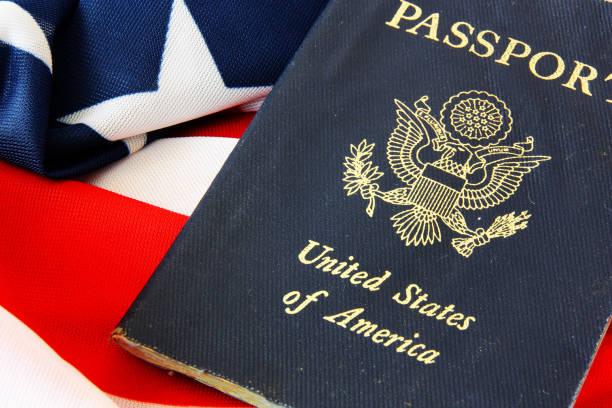 Pasaporte de Estados Unidos sobre el fondo de la bandera - foto de stock