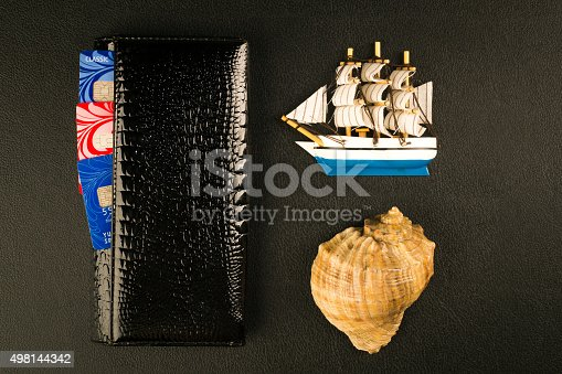 184640907istockphoto Passport, shell, wallet and sailfish - travel concept, black background 498144342