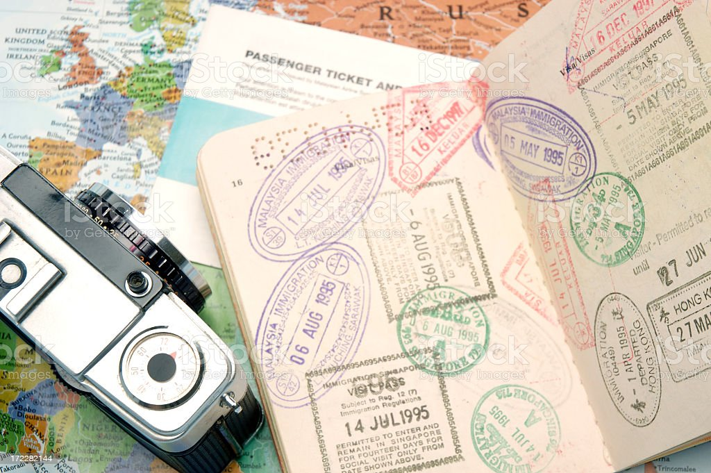 Passport travel stamps with a camera and world map stock photo
