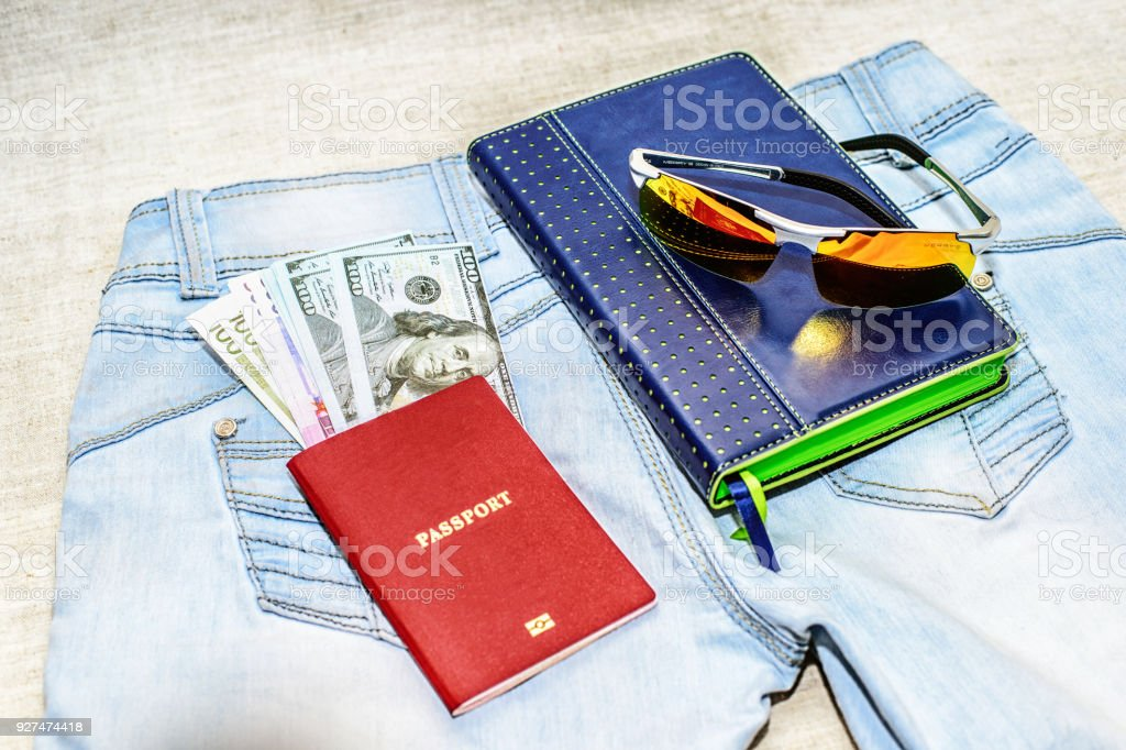 Passport with money bills, glasses and notepad lie on jeans. The concept of travel. stock photo