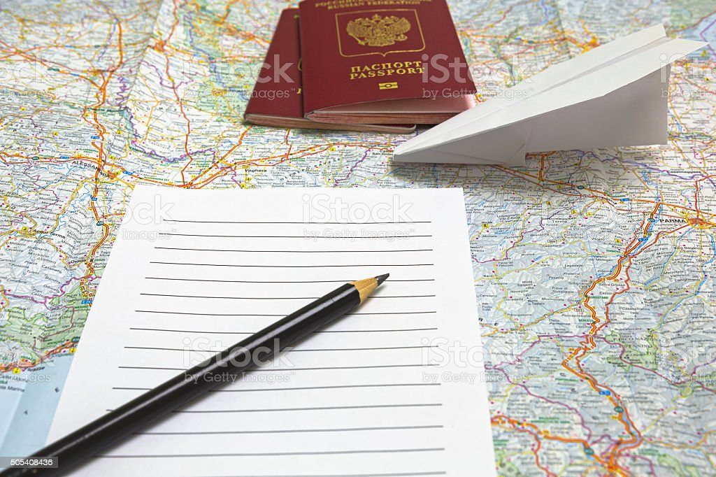 Passports, pencil, list of notebook, paper airplane on a map of...