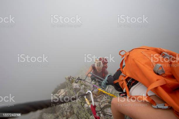 Photo of POV past carabiner to young woman climbing up a via ferrata in the mist