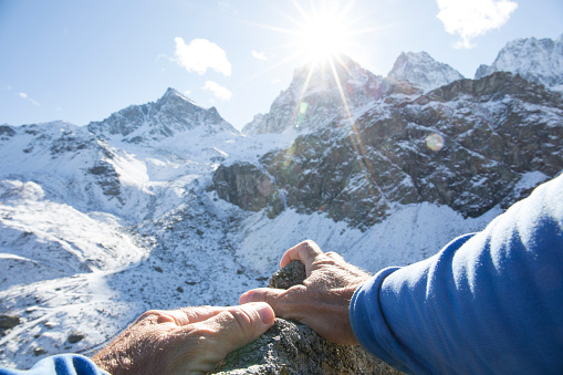 istock POV past climber hands on rock to mountains in distance 956845118
