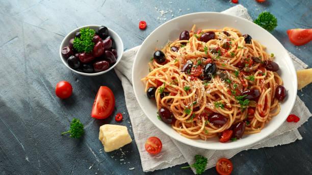 Pasta Alla Puttanesca with garlic, olives, capers, tomato and anchois fish stock photo