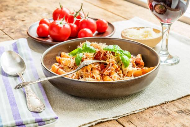 Massas All'Arrabbiata - um tradicional prato italiano com queijo parmesão e vinho tinto em um fundo rústico - foto de acervo