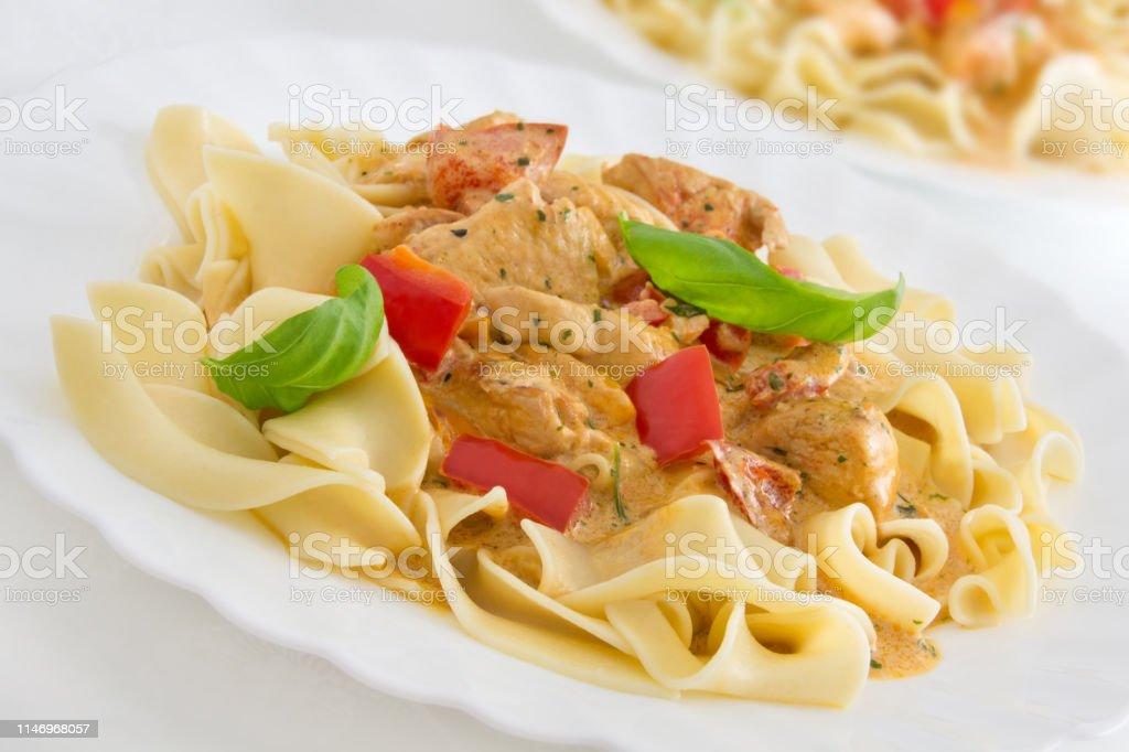 Pasta and creamy turkey meat stew background