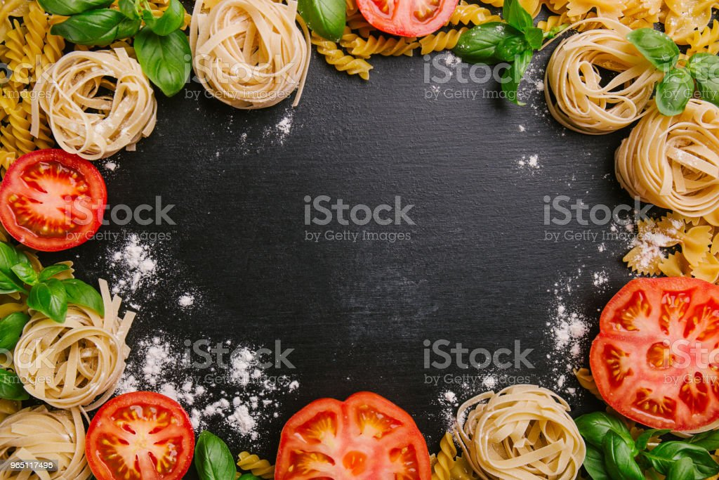 Pasta and fresh vegetables scattered in flour royalty-free stock photo
