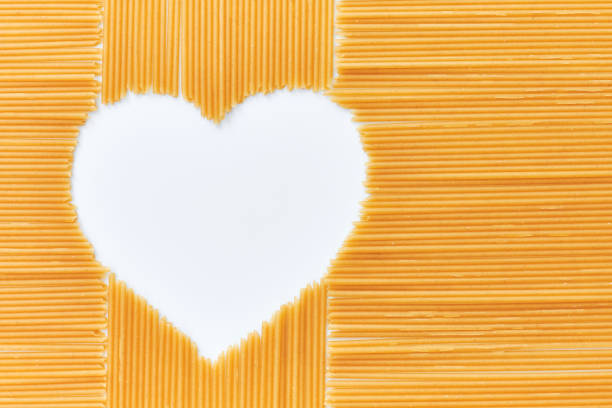 Pasta and Heart, the concept of love for pasta. Heart shaped inside long pasta. Space for your text. stock photo