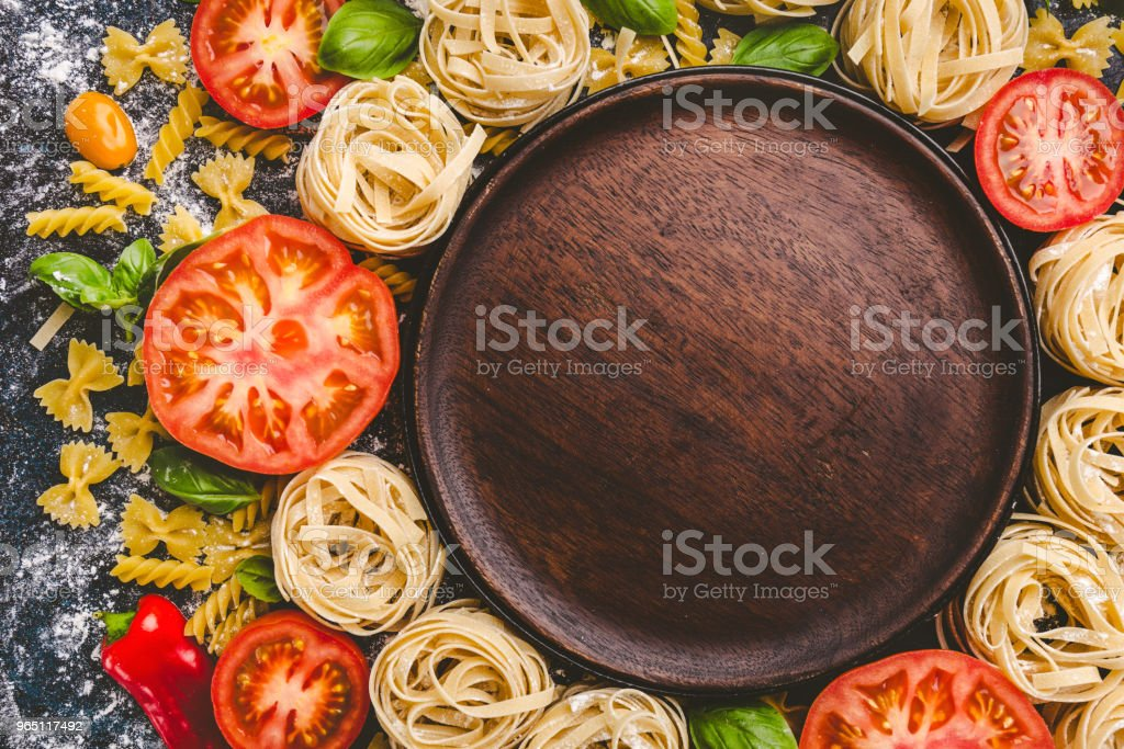 Pasta and vegetables scattered around wooden plate zbiór zdjęć royalty-free