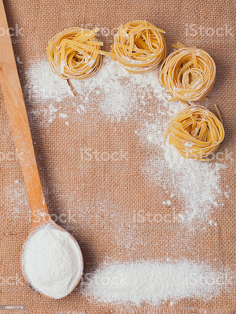 Pasta and wooden spoon with flour on sacking stock photo
