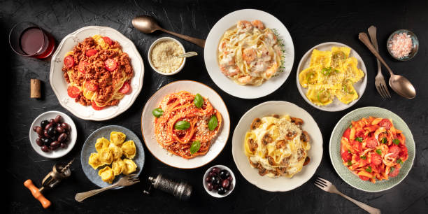 Pasta. Assortment of Italian pasta dishes, including spaghetti Bolognese, penne with chicken, tortellini, ravioli and others, shot from the top on a black background stock photo