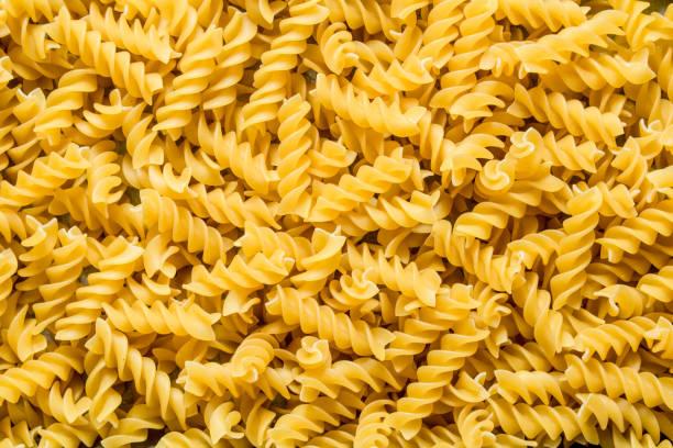 Pasta background. Dry pasta fusilli. Pasta background. Dry pasta fusilli. Top view fusilli stock pictures, royalty-free photos & images