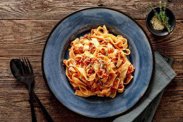 pasta bolognese. traditional italian dish of pasta with tomato and meat mince sauce served in a plate with parmesan cheese and thyme, top view - macarrão imagens e fotografias de stock
