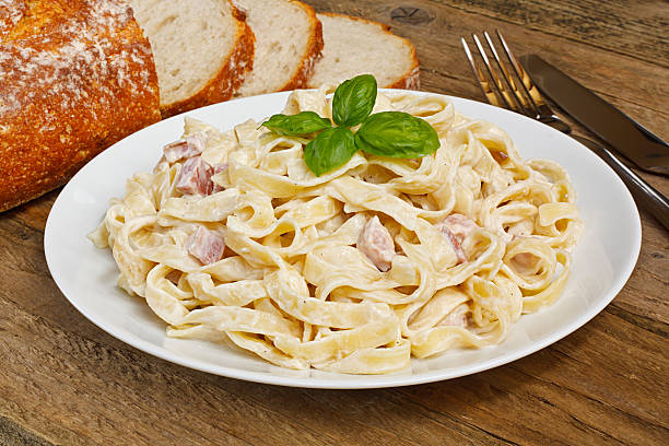 pasta carbonara Plate of tagliatelli carbonara italian food in a rustic restaurant setting tagliatelle stock pictures, royalty-free photos & images
