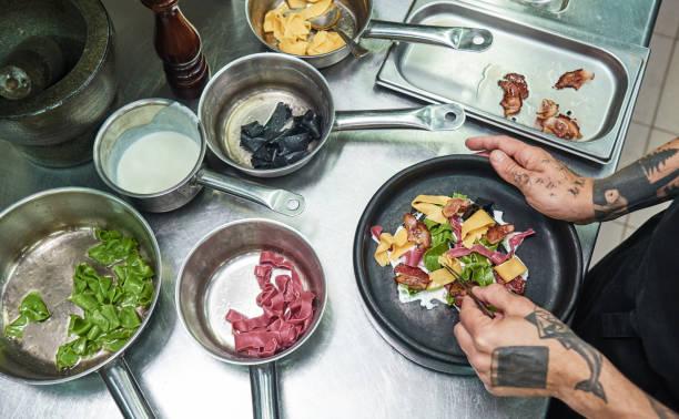 pasta carbonara. top-ansicht der hände des küchenchefs mit mehreren tattoos, die traditionelle italienische nudeln auf einem teller garnieren, während sie in einer küche stehen - italienische küchen dekor stock-fotos und bilder