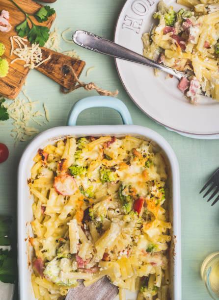 pasta-auflauf mit romanesco kohl und schinken in sahnesauce, serviert in platte mit gabel am küchentisch mit zutaten - gebackener blumenkohl stock-fotos und bilder