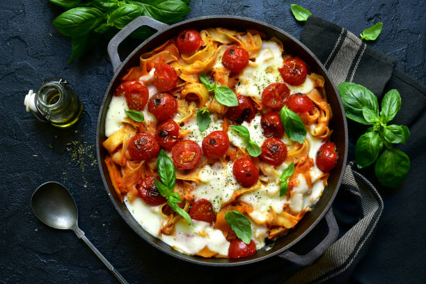 Pasta casserole with tomatoes and mozzarella cheese in a cast iron pan Pasta casserole with tomatoes and mozzarella cheese in a cast iron pan on a dark slate, stone or concrete background. Top view with copy space. tagliatelle stock pictures, royalty-free photos & images
