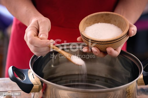 Pasta cooking - Hands holding wood bowl with salt, seasoning water with sea salt.