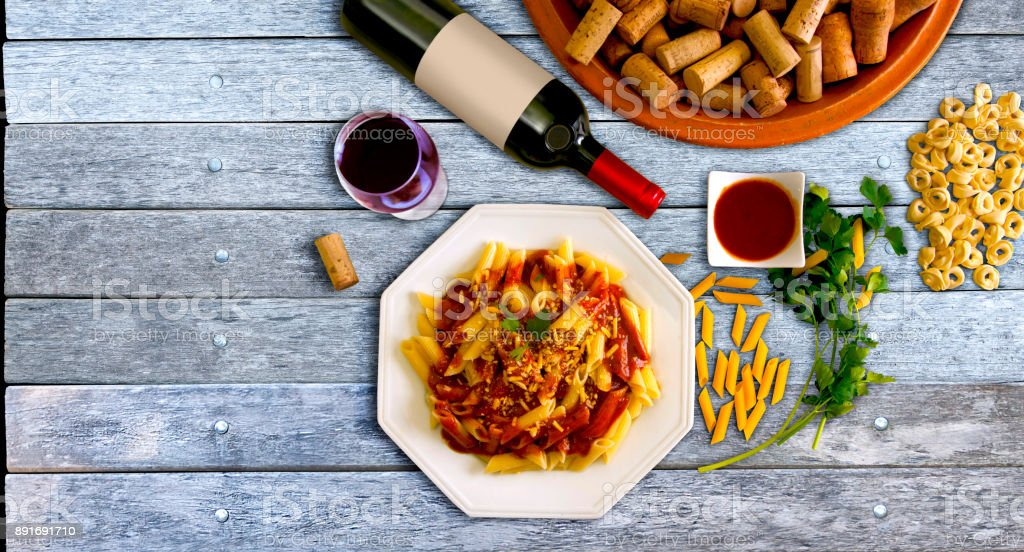 Pasta dish and bottle of wine with blank label in a wood table stock photo