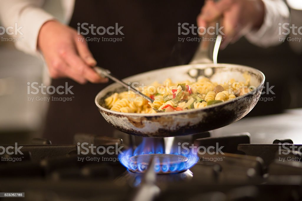 Pasta dish with vegetables on stove stock photo