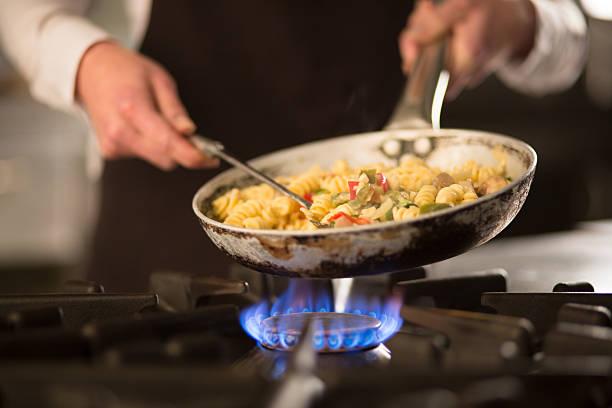 plat de pâtes et de légumes sur une plaque de cuisson - cuisinière photos et images de collection