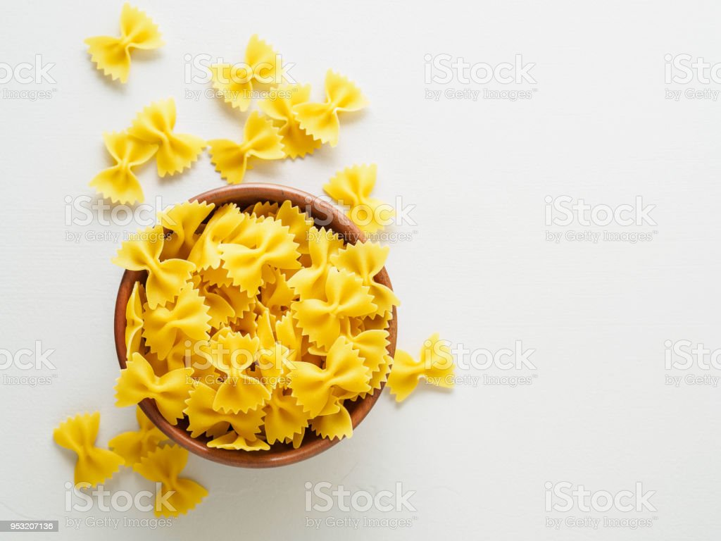 Pasta farfalle in wooden bowl on gray stone table. Top view, empty place for text. stock photo