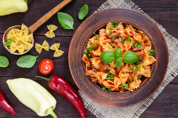 Pasta farfalle with chicken, tomato sauce and basil in a clay bowl on dark wooden background. The top view Pasta farfalle with chicken, tomato sauce and basil in a clay bowl on dark wooden background. The top view bow tie pasta stock pictures, royalty-free photos & images