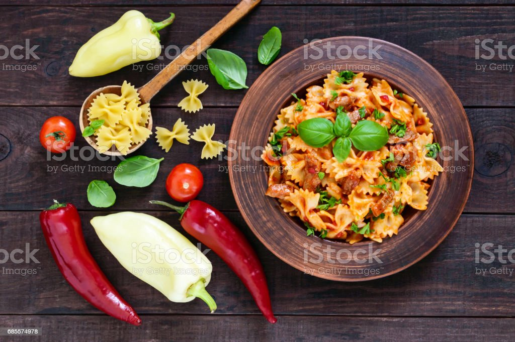 Pasta farfalle with chicken, tomato sauce and basil in a clay bowl on dark wooden background. The top view stock photo