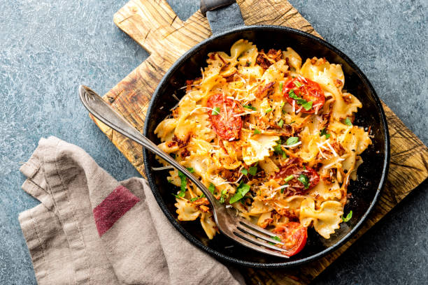 pasta farfalle with roasted meat and tomatoes in a frying pan pasta farfalle with roasted meat and tomatoes in a frying pan bow tie pasta stock pictures, royalty-free photos & images