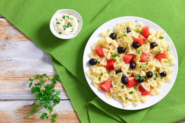 pasta Farfalle with Smoked Salmon and black olives delicious italian pasta Farfalle with Smoked Salmon and black olives sprinkled with parsley on white plate on old wooden table with cream sauce, view from above bow tie pasta stock pictures, royalty-free photos & images