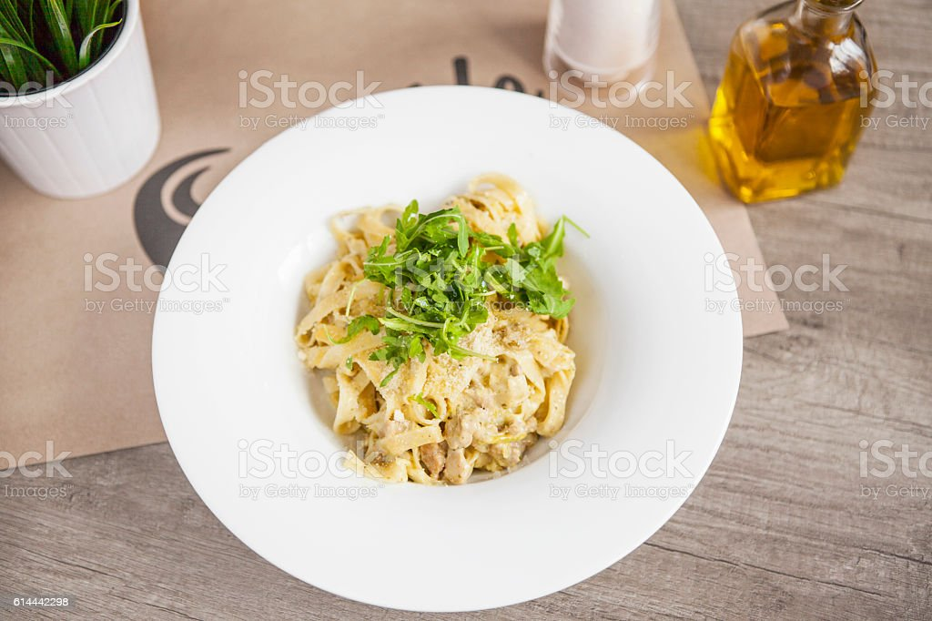 Pasta fettuccine alfredo with chicken, parmesan and parsley on w stock photo