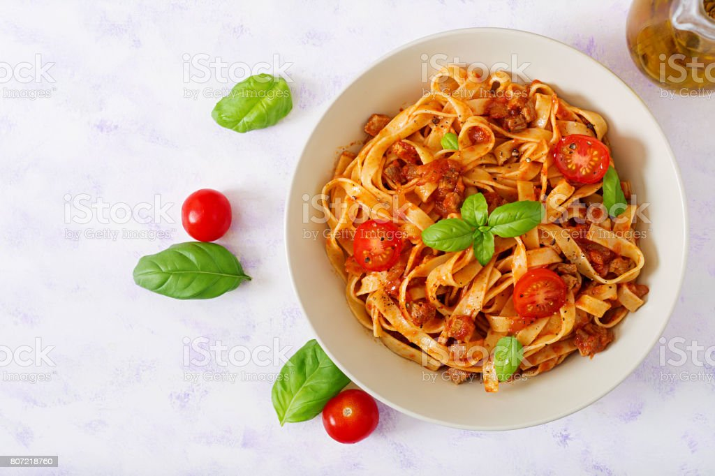 Pasta Fettuccine Bolognese with tomato sauce in white bowl. Flat lay. Top view stock photo