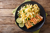 Pasta fetuccini with cheddar cheese and grilled salmon on a plate close-up. horizontal view from above