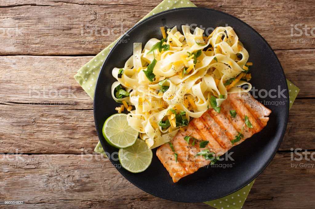 Pasta fetuccini with cheddar cheese and grilled salmon on a plate close-up. Horizontal top view stock photo