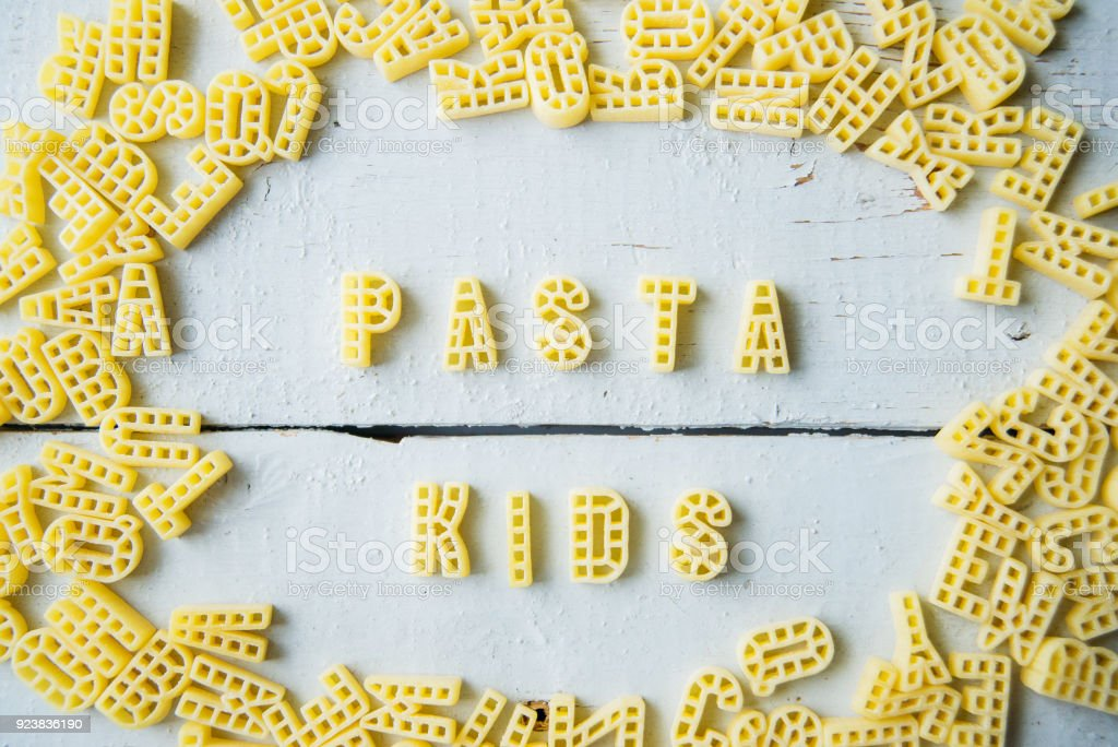 Pasta for kids. Word pasta alphabet. Wooden background. Empty copy space for text stock photo