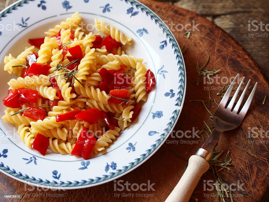 Pasta fusilli with sweet red peppers and rosemary aromatic herb stock photo