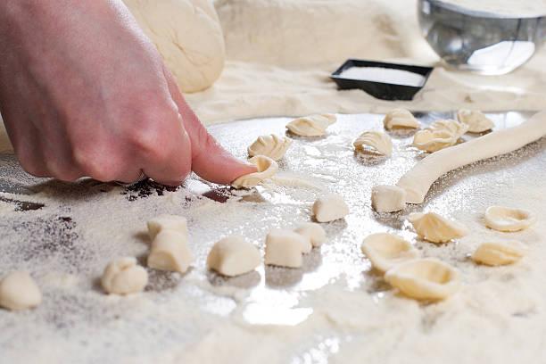 Pasta homemade Mani di donna preparano le orecchiette, primo piatto tipico della Puglia, realizzato con sale, acqua, farina di grano duro. orecchiette stock pictures, royalty-free photos & images