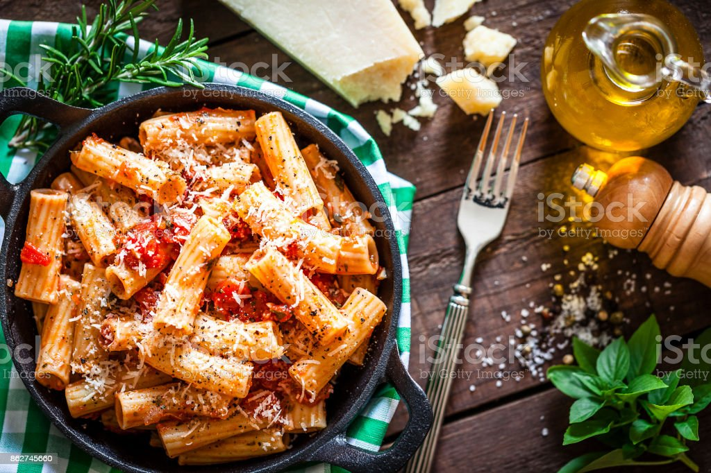 Pasta in a cast iron pan shot from above on rustic wooden table stock photo