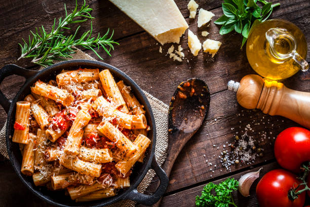 pasta in a cast iron pan shot from above on rustic wooden table - pasta foto e immagini stock