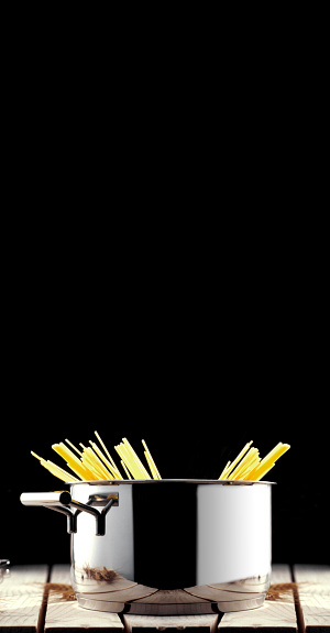 pasta in a pan in front of a black background
