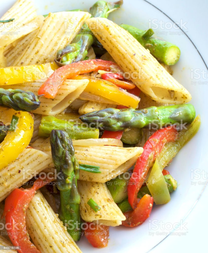Pasta in roasted asparagus, peppers with green pesto stock photo