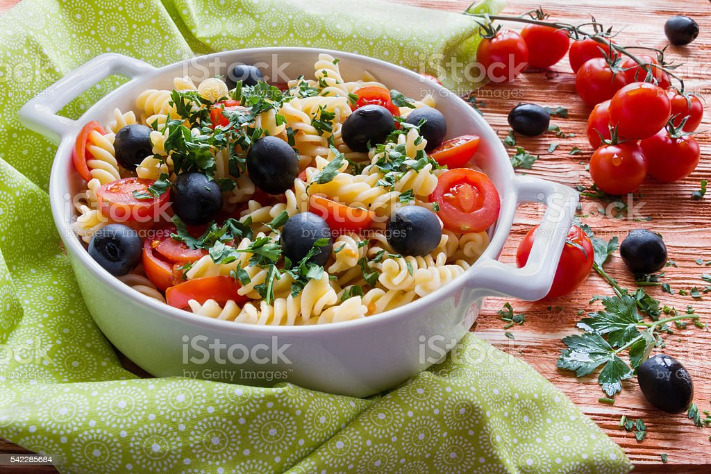 Pasta (fusilli) in white pan on wooden background stock photo