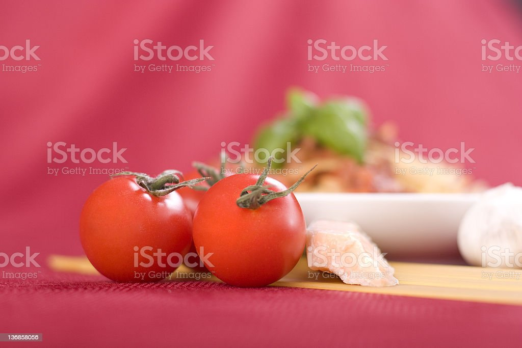 Pasta Ingredients Tomatoes, parmesan, and noodles sit in front of a bowl of spaghetti bolognese. Cheese Stock Photo