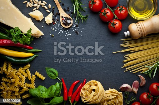 Ingredients for cooking traditional italian pasta shot on dark stone background. The ingredient are placed all around the frame leaving a useful copy space at the center. Composition includes tagliatelle pasta, spaghetti, olive oil, tomatoes, basil, rosemary, parsley,  pepper, salt, garlic and parmesan cheese. Low key DSRL studio photo taken with Canon EOS 5D Mk II and Canon EF 100mm f/2.8L Macro IS USM