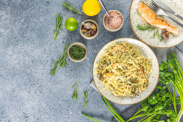 Pasta linguine with mushrooms, shrimps and seafood mussels, cheese and herbs, in ceramic plate on a light gray surface. stock photo