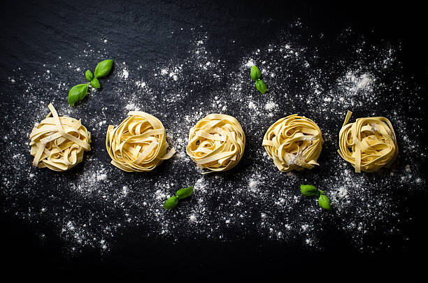 Pasta on dark background Pasta on dark background tagliatelle stock pictures, royalty-free photos & images