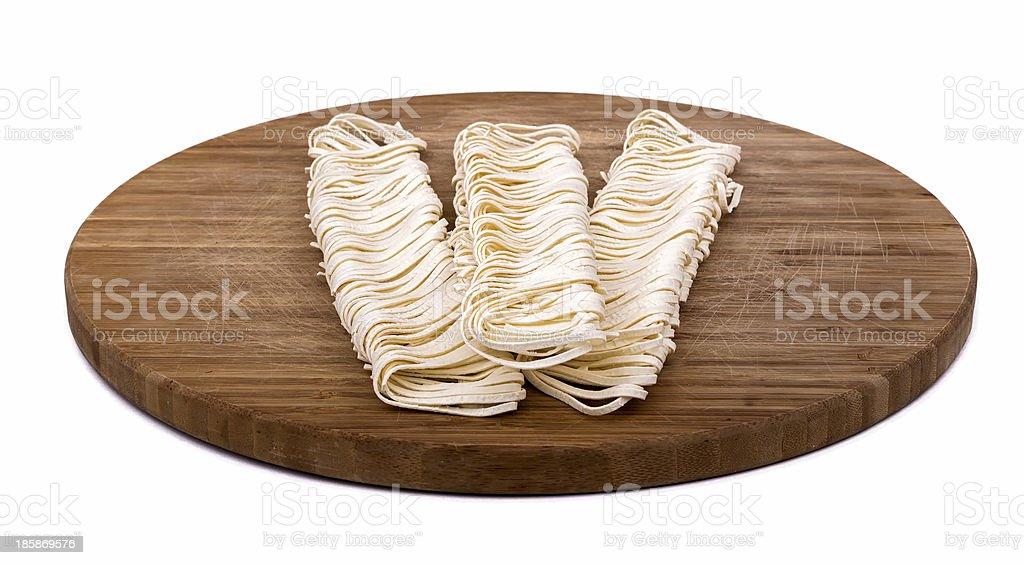 Pasta auf hölzernen Schneidebrett. Weißer Hintergrund – Foto