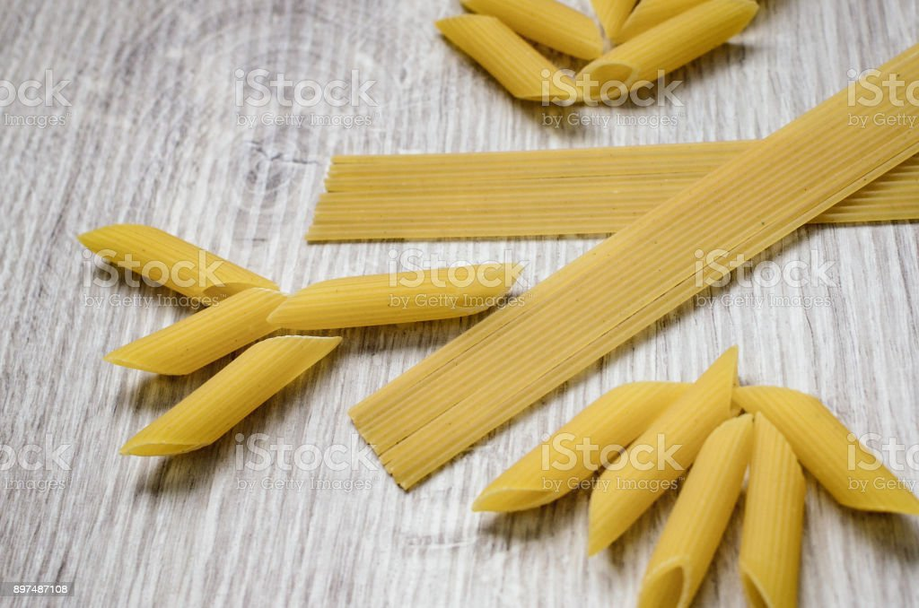 Pasta penne, macaroni isolated on a wooden background. Top view stock photo