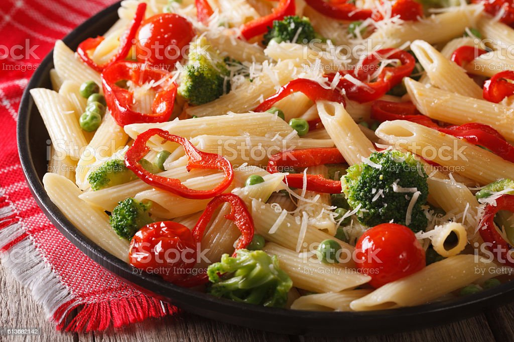Pasta Penne Primavera with vegetables close-up. horizontal stock photo